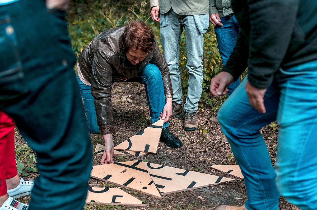 Collega's helpen elkaar tijdens een outdooractiviteit bij Landhuis de Oliphant in Rotterdam.